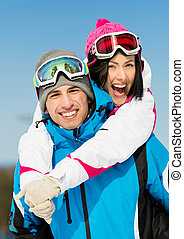 Happy couple of alps skiers have fun