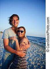 Happy couple of lovers on the seashore.