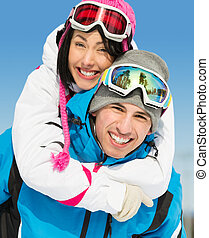 Happy couple of mountain skiers have fun