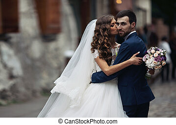 Happy couple of newlyweds valentynes posing and hugging in old europeand street with bouquet b&wHappy couple of newlyweds valentynes posing and hugging in old europeand street with bouquet
