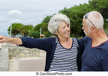 happy couple of seniors looking at the sea