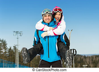 Happy couple of skiers have fun