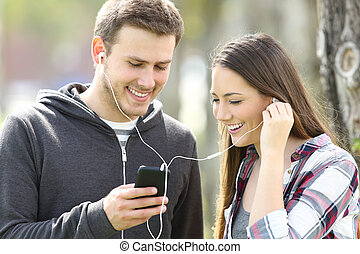 Happy couple of teenagers sharing music