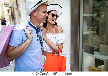Happy couple of tourists shopping in the city on vacation