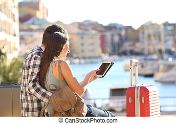 Happy couple of tourists using a tablet on vacation