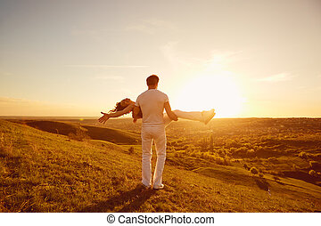 Happy couple on a beautiful sunset in nature