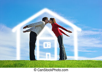 Happy couple on a green meadow and house