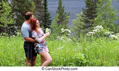 happy couple on a green meadow by the lake enjoying the beauty of the surrounding