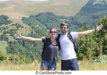 Happy couple on a hiking trip surrounded by mountains