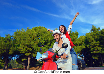 Happy couple on a scooter at summer vacation