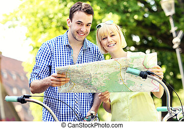 Happy couple on bikes with a map