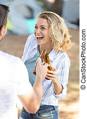 happy couple on camping holding chink their beer bottles