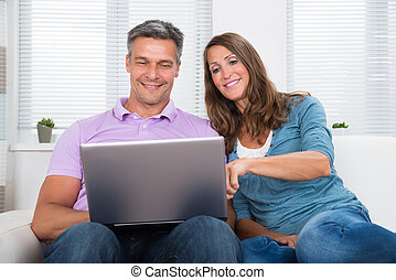 Couple On Sofa Using Laptop