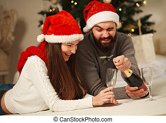 Happy couple on the background of the Christmas tree at home celebrating by opening a bottle of champagne