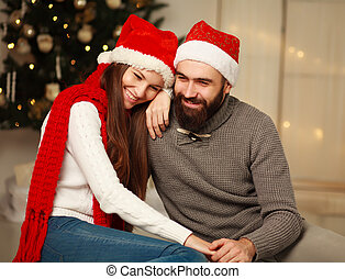 Happy couple on the background of the Christmas tree at home