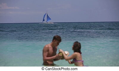 Happy couple on the beach with coconut
