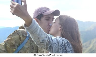 Happy couple on the mountain top taking selfie photo while...