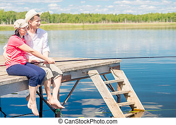 happy couple on the pier with bare feet catching fish on a beautiful lake