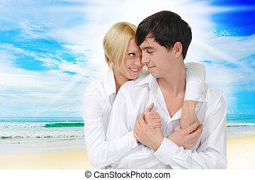 Happy couple on the sunny beach