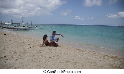 Happy couple on tropical beach. - Happy young couple sitting...