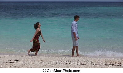Happy couple on tropical beach - A young man stands on the...