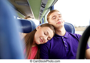 happy couple or passengers sleeping in travel bus -...