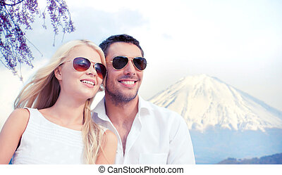 summer holidays and dating concept - couple in shades over fuji mountain background