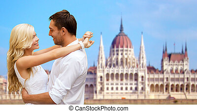 happy couple over house of parliament in budapest