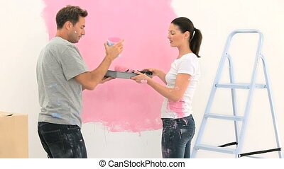 Happy couple painting a wall in pink