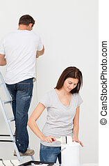 Happy couple painting together a room in white