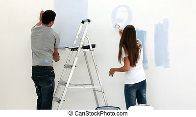 Happy couple painting wall in blue in their bedroom