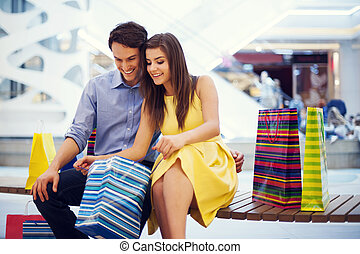 Happy couple peeking into shopping bag