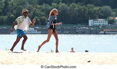 Happy couple playing and running on beach shore
