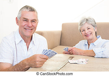 Happy couple playing cards