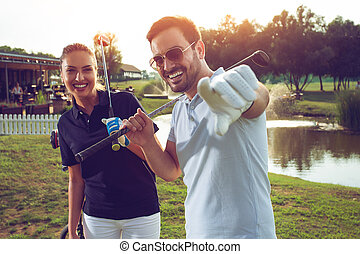 Happy couple playing golf at the club
