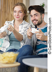 happy couple playing video games with joystick sitting on sofa