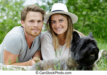 happy couple playing with a dog in the park