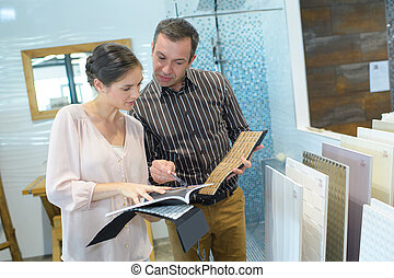 happy couple pointing at ceramic tile