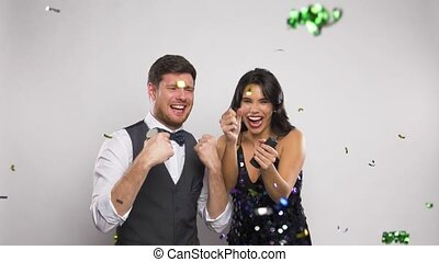 happy couple popping party poppers and having fun -...