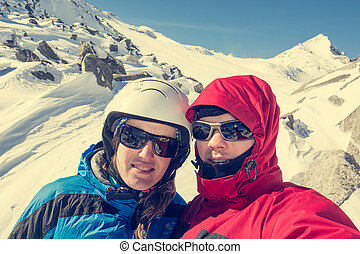 Happy couple posing on a skiing trip to the mountains.