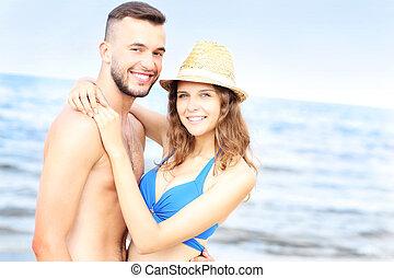 Happy couple posing over the sea
