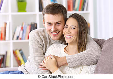 Happy couple posing together on a couch at home