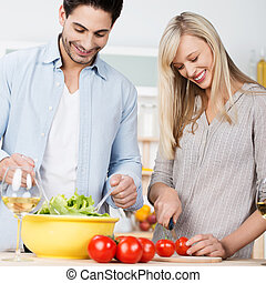 Happy couple preparing a fresh salad