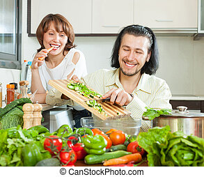 Happy couple preparing a meal of vegetables