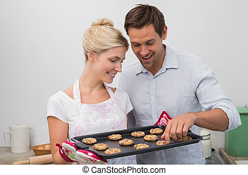 Happy couple preparing cookies together in kitchen