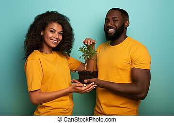 Happy couple protect a small tree. Concept of forestation, ecology and conservation
