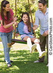 Happy couple pushing daughter on swing