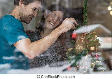 Happy couple putting up Christmas decorations