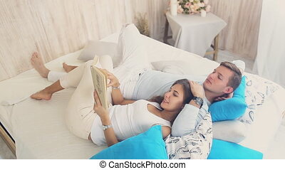 happy couple reading a book lying on the bed