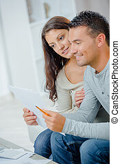 happy couple reading a letter on a couch at home